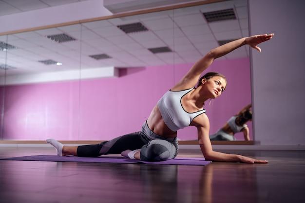 Passen sie junge kaukasische brünette in sportbekleidung an, die auf matte im fitnessstudio sitzt und seitenstrecken tut.