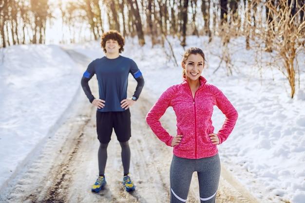 Passen sie schöne kaukasische sportliche brünette in sportbekleidung an, die auf der straße mit den händen auf den hüften steht und sich nach dem laufen ausruht. im hintergrund ruht sich auch ihr männlicher freund aus. winter. fitness im freien.