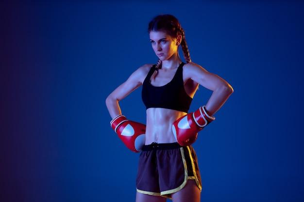 Passende kaukasische frau im sportbekleidungsboxen auf blauem hintergrund im neonlicht.