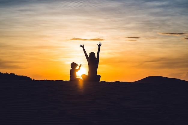 Passende mutter mit sohn, der an der wüste in gran canaria, maspalomas am sonnenuntergang läuft.