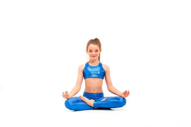 Passendes mädchen der junge, das yogaübungen auf weiß tut