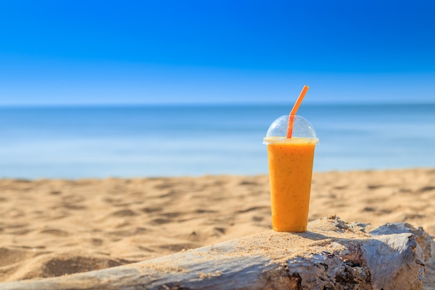 Passionsfruchtsaft mit strohhalm im glas am sandstrand bei phuket thailand. sommerkonzept