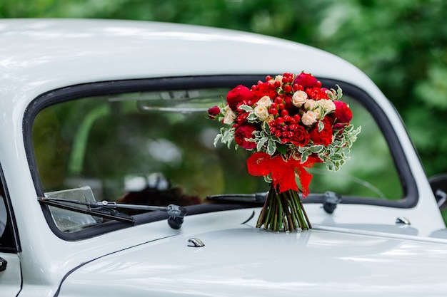 Passionshochzeitsstrauß mit dunkelroten und marsala-rosen, grün, das auf weißem auto steht
