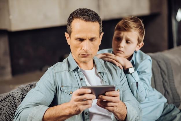 Passt auf. verärgerter jugendlicher junge, der sich auf dem sofa an seinen vater kuschelt und ihn am telefon spielen sieht, während der mann ihm keine aufmerksamkeit schenkt