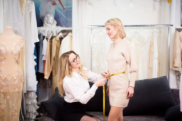Passt perfekt. weiblicher modedesigner und kunde, der die ärmellänge für maßgeschneiderte kleidung im atelier misst.
