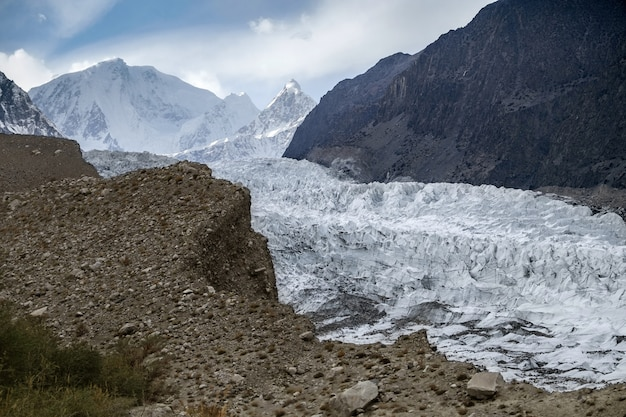 Passu-gletscher gegen schnee mit einer kappe bedeckte berge in karakoram-strecke