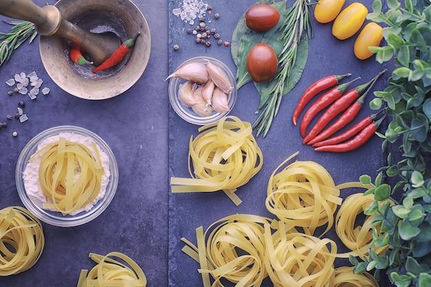 Pasta auf dem tisch mit gewürzen und gemüse. nudeln mit gemüse zum kochen auf schwarzem steinhintergrund.