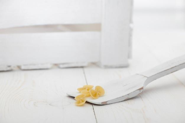 Pasta auf einem holzlöffel und einer schachtel auf einem weißen alten holzbrett