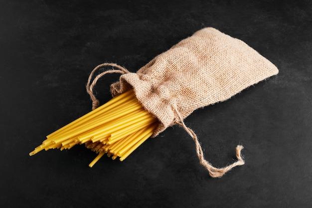 Pasta auf schwarz in einem sackleinenpaket.