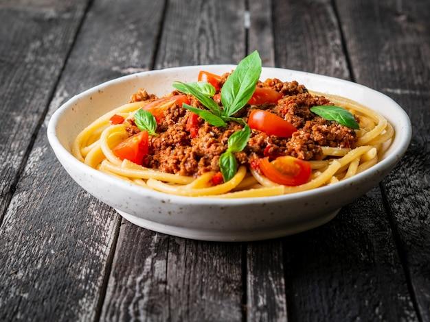 Pasta bolognese mit tomatensauce, hackfleisch, basilikumblatt