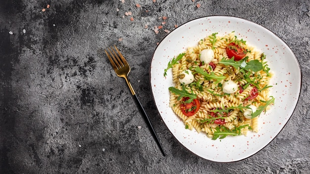 Pasta caprese salat mit tomaten, mozzarella. langes bannerformat, ansicht von oben.