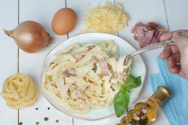 Pasta carbonara auf einem teller mit zutaten in der nähe des tellers, auf einem weißen holztisch stehend, hand mit einer gabel zieht tolyatelle.