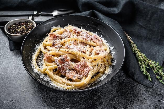 Pasta carbonara auf schwarzem teller mit parmesan-bucatini