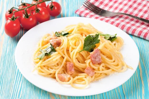 Pasta carbonara mit schinken und käse auf blauem holztisch. ansicht von oben.