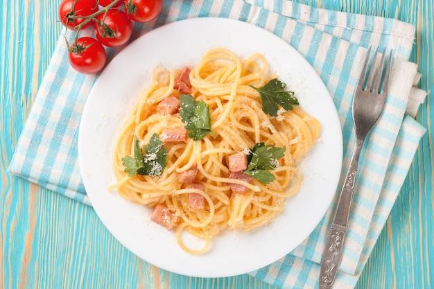 Pasta carbonara mit schinken und käse auf blauem holztisch. draufsicht.