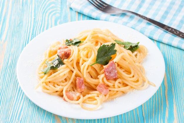 Pasta carbonara mit schinken und käse auf blauer holzoberfläche. draufsicht.