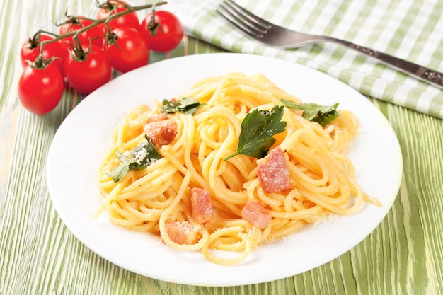 Pasta carbonara mit schinken und käse auf grünem holztisch. draufsicht.