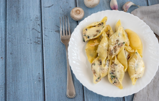 Pasta conchiglioni mit pilzen in einem weißen teller auf holzoberfläche