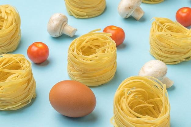 Pasta, ei, tomaten und pilze auf einer blauen oberfläche. zutaten für die herstellung von nudeln.