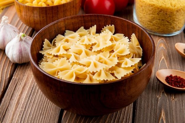 Pasta farfale in der seitenansicht des hölzernen schüssel-tomaten-knoblauchs
