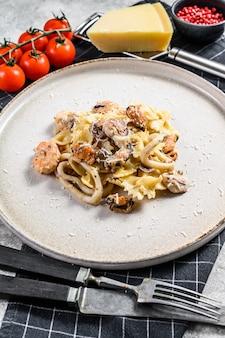 Pasta farfale mit meeresfrüchten. grauer hintergrund. draufsicht.