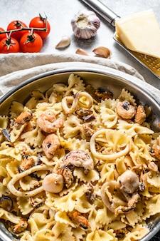 Pasta farfale mit meeresfrüchten in einer pfanne. tintenfisch, garnelen, tintenfisch, jakobsmuschel und muscheln. grauer hintergrund. draufsicht