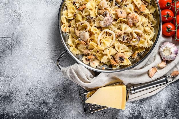 Pasta farfale mit meeresfrüchten, tintenfisch, garnelen, tintenfisch, jakobsmuschel und muscheln. grauer hintergrund. draufsicht. platz für text