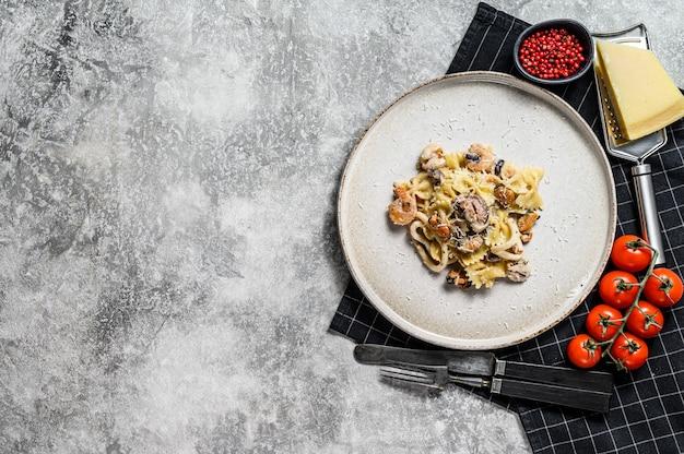 Pasta farfale mit tintenfisch, garnelen, tintenfisch, jakobsmuschel und muscheln. gesunde meeresfrüchte. grauer hintergrund. draufsicht. platz für text