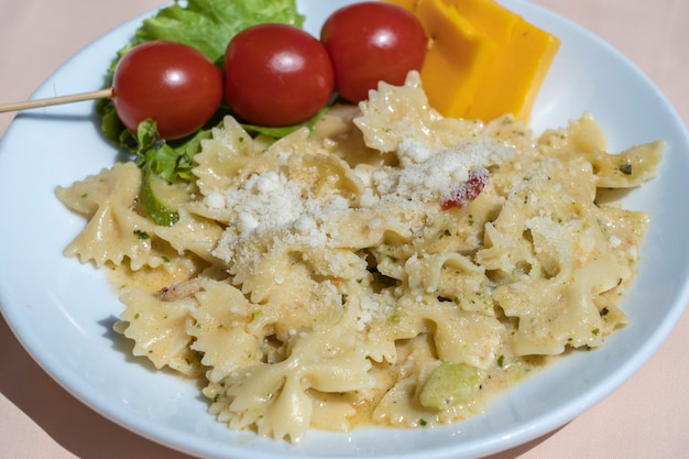 Pasta farfalle mit kirschtomaten und käse in weißer platte, nahaufnahme