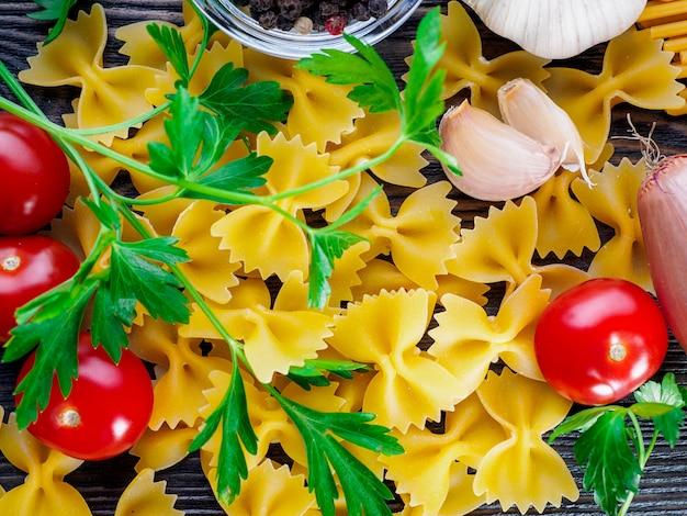 Pasta farfalle, schmetterlingsform, tomaten, schalotten, knoblauch, petersilie auf dunklem hintergrund