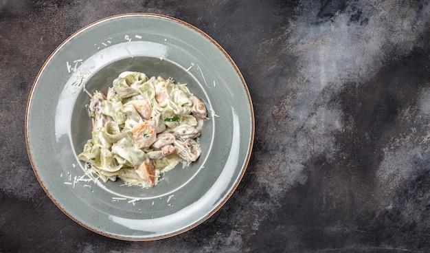 Pasta fettuccine alfredo mit champignons und gebratenem hühnerfleisch in cremiger käsesauce. tagliatelle-nudeln. traditionelles italienisches gericht. banner, menü, rezeptplatz für text, ansicht von oben.