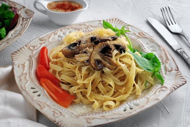 Pasta fettuccine bolognese mit pilzen und gemüse auf weißem teller. menükonzept.