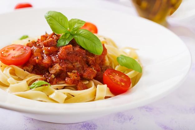 Pasta fettuccine bolognese mit tomatensauce in weißer schüssel.