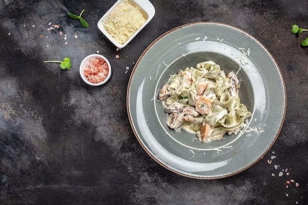 Pasta fettuccine mit champignons und gebratenem hühnerschinken in cremiger käsesauce. tagliatelle-nudeln. traditionelle italienische küche. banner, menü, rezeptplatz für text, ansicht von oben.