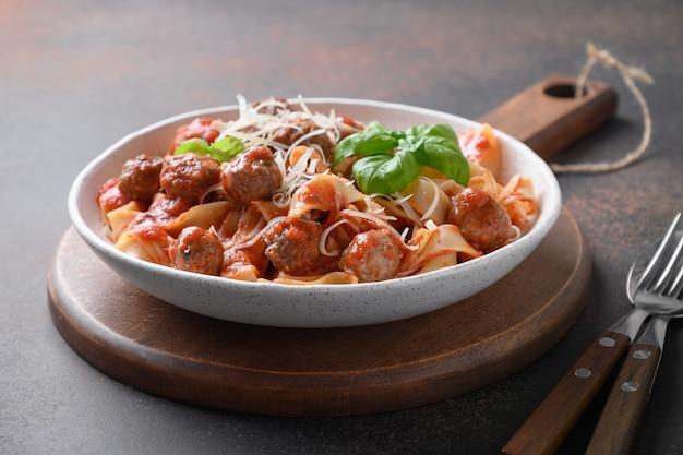 Pasta fettuccine mit fleischbällchen und tomatensauce in einer schüssel
