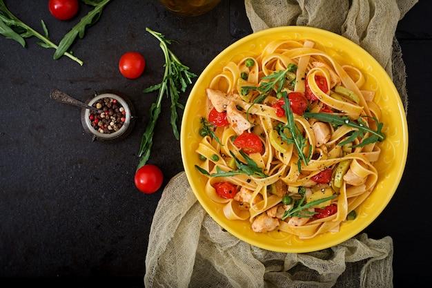 Pasta fettuccine mit tomaten, zucchini und hähnchenfilet in schüssel. flach liegen. ansicht von oben
