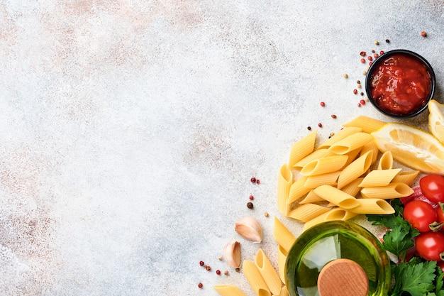 Pasta-hintergrund. pasta rigati, tomatenketchupsauce, olivenöl, gewürze, petersilie und frische tomaten auf einem hellgrauen schiefertisch. essen kochen hintergrund. draufsicht mit kopienraum.