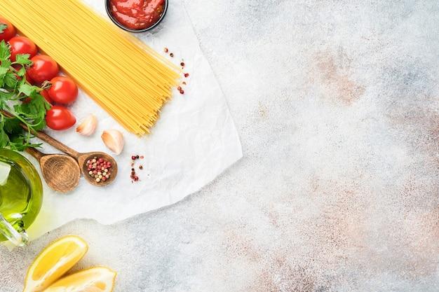 Pasta-hintergrund. pasta spaghetti, tomatenketchupsauce, olivenöl, gewürze, petersilie und frische tomaten auf einem hellgrauen schiefertisch. essen kochen hintergrund. draufsicht mit kopienraum.