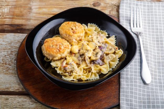 Pasta in einer cremigen sauce mit pilzen und hühnerfleischbällchen in einem schwarzen teller auf einer serviette neben einer gabel. horizontales foto