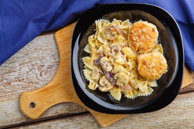 Pasta in einer cremigen sauce mit pilzen und hühnerfleischbällchen in einem teller auf einem brett auf einer blauen serviette. horizontales foto
