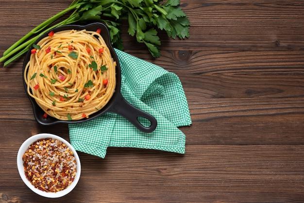 Pasta in einer pfanne auf dunklem holzhintergrund mit gemüse. ansicht von oben.