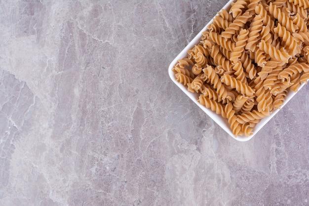 Pasta in einer weißen keramikplatte auf dem marmor