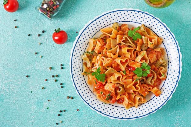 Pasta in form von herzen mit huhn und tomaten in tomatensauce. ansicht von oben