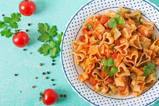 Pasta in form von herzen mit huhn und tomaten in tomatensoße. draufsicht