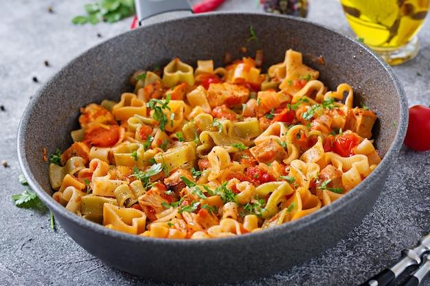 Pasta in form von herzen mit huhn und tomaten in tomatensoße.