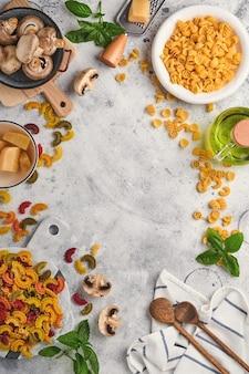 Pasta. italienische pasta. insalata di pasta und gemüse kochen zutaten, käse, pilze und basilikum auf altem steinhintergrund. zutaten zum kochen des italienischen essens. draufsicht mit kopienraum.