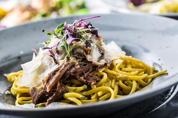 Pasta linguine mit confit entenbrust parmesan und kräuterdekoration.
