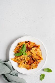 Pasta maltagliati mit klassischer tomatensauce, parmesan und basilikum auf rustikalem beton