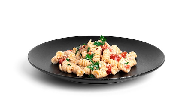 Pasta mit feta-käse, tomaten und kräutern isoliert.