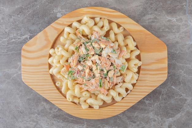 Pasta mit frischem salat auf holzplatte.
